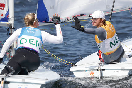 First placed Netherlands' Marit Bouwmeester, right, greets third placed Denmark's Anne-Marie Rindom at the end of the Laser Radial Women event during the 2016 Summer Olympics in Rio de Janeiro, Brazil