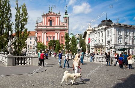 Stock Photo of Tourists and residents walk over Tromostovje bridges in downtown Ljubljana, Slovenia. Over the past two decades since Melanija Knavs, who later changed her name to Melania Knauss, left her native Slovenia and married American billionaire Donald Trump after pursuing an international modeling career, Ljubljana has turned from a gray and drab place with almost no night life, into a lively and picturesque city filled with restaurants, cafes and night clubs packed with foreigners