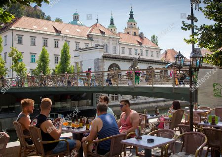 Stock Picture of A group of tourists drink beers in downtown Ljubljana, Slovenia. Over the past two decades since Melanija Knavs, who later changed her name to Melania Knauss, left her native Slovenia and married American billionaire Donald Trump after pursuing an international modeling career, Ljubljana has turned from a gray and drab place with almost no night life, into a lively and picturesque city filled with restaurants, cafes and night clubs packed with foreigners