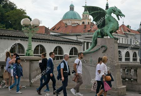 Stock Image of Tourists and residents walk by a statue of a dragon, a symbol of the city, in downtown Ljubljana, Slovenia. Over the past two decades since Melanija Knavs, who later changed her name to Melania Knauss, left her native Slovenia and married American billionaire Donald Trump after pursuing an international modeling career, Ljubljana has turned from a gray and drab place with almost no night life, into a lively and picturesque city filled with restaurants, cafes and night clubs packed with foreigners