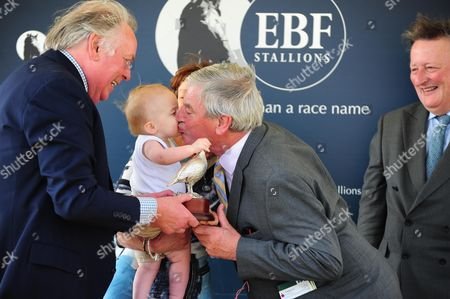 YORK. Young Henry Wooley, grandson of Lady Jane Cecil gets a kiss from Peter Reynolds of Ballymacoll Stud, after ABINGDON and Andrea Atzeni won for trainer Sir Michael Stoute.