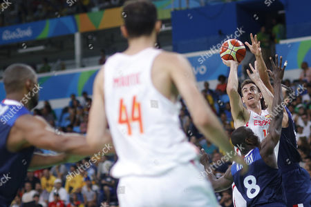 Spain's Victor Claver on the right of the image drives over France's Charles Kahudi (8) and Joffrei Lauverge during a men's quarterfinal round basketball game at the 2016 Summer Olympics in Rio de Janeiro, Brazil, Wednesday, Aug. 17, 2016.