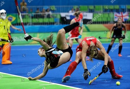 New Zealand's Rose Keddell, left, falls as she fights for the ball with Britain's Crista Cullen, right, during a women's field hockey semifinal match at 2016 Summer Olympics in Rio de Janeiro, Brazil