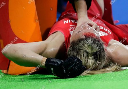 Britain's Crista Cullen, lies on the ground after she get injured on her head during a women's field hockey semifinal match against New Zealand at 2016 Summer Olympics in Rio de Janeiro, Brazil