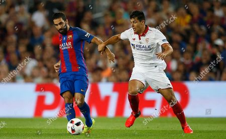 Arda Turan, Benoit Tremoulinas FC Barcelona's Arda Turan, left, duels for the ball against Sevilla's Benoit Tremoulinas during the Spanish Super Cup final soccer match between FC Barcelona and Sevilla at the Camp Nou in Barcelona, Spain