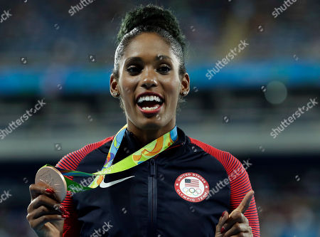 Bronze medal winner Kristi Castlin from the United States shows off her medal during the medal ceremony for the women's 100-meter hurdles at the athletics competitions of the 2016 Summer Olympics at the Olympic stadium in Rio de Janeiro, Brazil