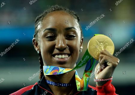 Gold medal winner Brianna Rollins from the United States shows off her medal during the medal ceremony for the women's 100-meter hurdles final during the athletics competitions of the 2016 Summer Olympics at the Olympic stadium in Rio de Janeiro, Brazil