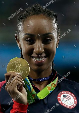 Gold medal winner Brianna Rollins from the United States shows off her bronze medal during the medal ceremony for the women's 100-meter hurdles at the athletics competitions of the 2016 Summer Olympics at the Olympic stadium in Rio de Janeiro, Brazil
