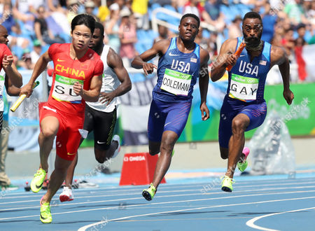 United States' Tyson Gay, right, takes the baton from Christian Coleman, center, as they competes in a men's 4x100-meter relay heat during the athletics competitions of the 2016 Summer Olympics at the Olympic stadium in Rio de Janeiro, Brazil