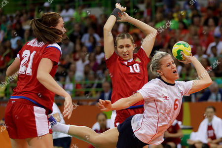 Norway's Heidi Loke, right, scores a goal besides Russia's Victoria Zhilinskayte, left, and Russia's Olga Akopian during the women's semifinal handball match between Norway and Russia at the 2016 Summer Olympics in Rio de Janeiro, Brazil