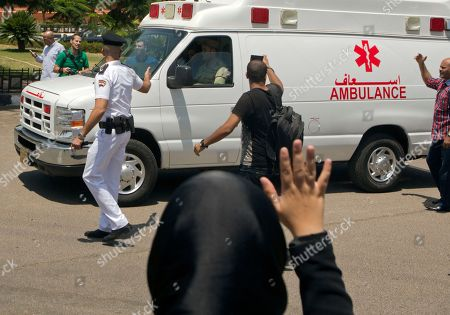 An Egyptian mourner waves to an ambulance carrying the coffin of Egyptian-American Nobel Laureate Ahmed Zewail at Cairo International Airport, in Cairo, Egypt