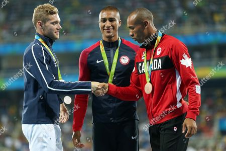 United States' gold medal winner Ashton Eaton is flanked by France's silver medal winner Kevin Mayer and Canada's bronze medal winner Damian Warner celebrate during the medal ceremony for the decathlon, in the athletics competitions of the 2016 Summer Olympics at the Olympic stadium in Rio de Janeiro, Brazil, Friday, Aug. 19, 2016