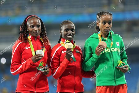 Kenya's gold medal winner Vivian Jepkemoi Cheruiyot is flanked by Kenya's silver medal winner Hellen Onsando Obiri and Ethiopia's bronze medal winner Almaz Ayana during the athletics competitions of the 2016 Summer Olympics at the Olympic stadium in Rio de Janeiro, Brazil, Friday, Aug. 19, 2016