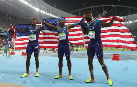 Members of the United States team from left, United States' Justin Gatlin, United States' Mike Rodgers and United States' Tyson Gay celebrate after the men's 4x100-meter relay final during the athletics competitions of the 2016 Summer Olympics at the Olympic stadium in Rio de Janeiro, Brazil