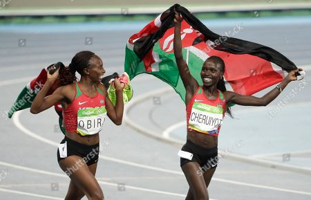 Kenya's Vivian Jepkemoi Cheruiyot, right, celebrates winning the gold medal and setting a new Olympic record in the women's 5000-meter final with silver medalist Kenya's Hellen Onsando Obiri during the athletics competitions of the 2016 Summer Olympics at the Olympic stadium in Rio de Janeiro, Brazil