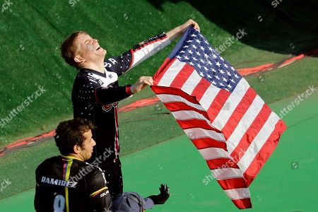Connor Fields of the United States, top, celebrates after winning gold in the men's BMX cycling final next to third placed Carlos Ramirez Yepes of Colombia, bottom, during the 2016 Summer Olympics in Rio de Janeiro, Brazil