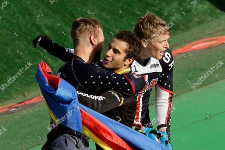 Third placed Carlos Ramirez Yepes of Colombia, center, hugs second placed Nicholas Long of the United States, left, as first placed Connor Fields of the United States, right, stands by them after the men's BMX cycling final during the 2016 Summer Olympics in Rio de Janeiro, Brazil