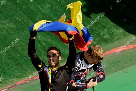 Third placed Carlos Ramirez Yepes of Colombia, left, waves a Colombian flag next to first placed Connor Fields of the United States after the men's BMX cycling final during the 2016 Summer Olympics in Rio de Janeiro, Brazil