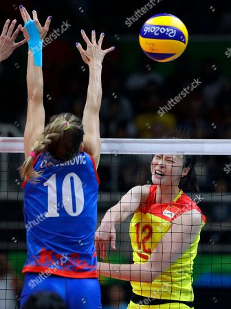 China's Hui Ruoqi, right, spikes the ball past Serbia's Maja Ognjenovic during a women's gold medal volleyball match at the 2016 Summer Olympics in Rio de Janeiro, Brazil