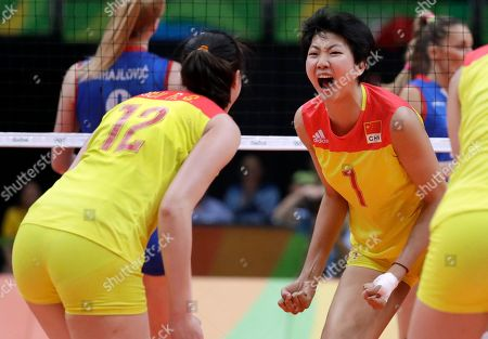 China's Yuan Xinyue, right, celebrates with teammate Hui Ruoqi (12) during a women's gold medal volleyball match against Serbia at the 2016 Summer Olympics in Rio de Janeiro, Brazil