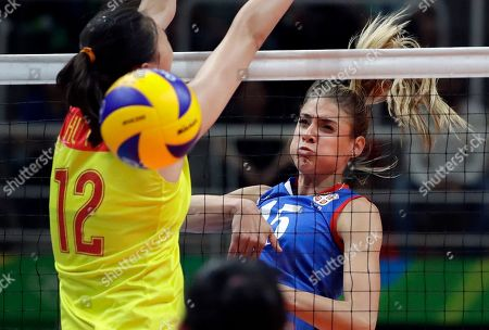 Serbia's Jovana Stevanovic, right, spikes the ball past China's Hui Ruoqi during a women's gold medal volleyball match at the 2016 Summer Olympics in Rio de Janeiro, Brazil