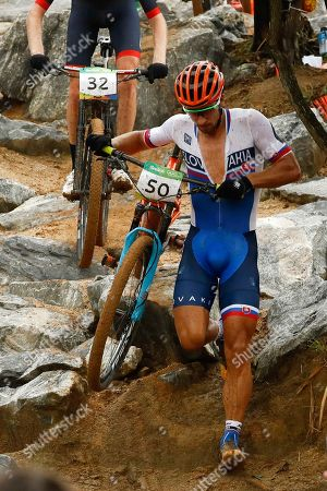 Peter Sagan of Slovakia walks down a rocky hill with his bicycle during in the men's cross-country cycling mountain bike race at the 2016 Summer Olympics in Rio de Janeiro, Brazil