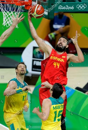 Spain's Nikola Mirotic (44) grabs a rebound over Australia's David Andersen, left, and Damian Martin, right, during the bronze medal basketball game at the 2016 Summer Olympics in Rio de Janeiro, Brazil