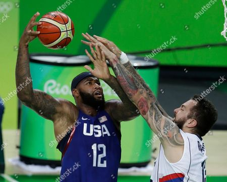 United States' DeMarcus Cousins (12) is fouled by Serbia's Miroslav Raduljica (13) during the men's gold medal basketball game at the 2016 Summer Olympics in Rio de Janeiro, Brazil