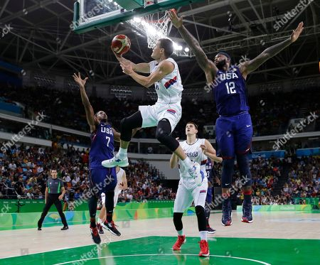Serbia's Nemanja Nedovic (11) drives to the basket as United States' DeMarcus Cousins (12) and United States' Kyle Lowry (7) defend during the men's gold medal basketball game at the 2016 Summer Olympics in Rio de Janeiro, Brazil