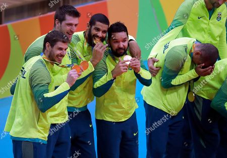 Members of Brazil's team, from left to right, Bruno Rezende, Eder Carbonera, Wallace de Souza, William Arjona and Sergio Dutra Santos celebrate after receiving their gold medals during the medal ceremony for men's volleyball at the 2016 Summer Olympics in Rio de Janeiro, Brazil