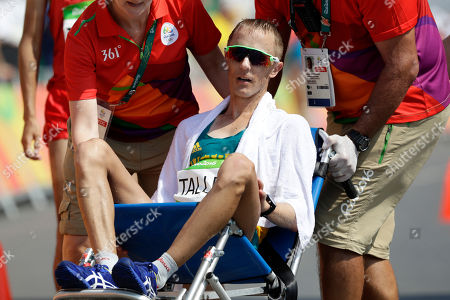 Jared Tallent, of Australia, is taken off the course in wheelchair after finishing second in the men's 50-km race walk at the 2016 Summer Olympics in Rio de Janeiro, Brazil