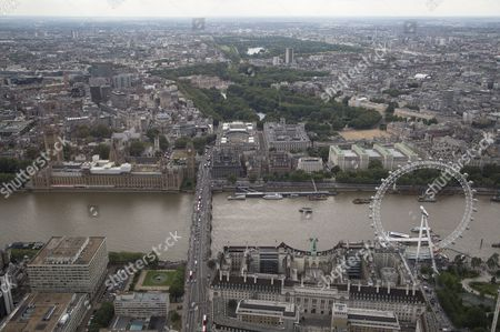 The London Eye/Millennium Wheel and The London Aquarium (below right) below The River Thames and Westminster Bridge and The Palace of Westminster (Elizabeth Tower/Big Ben, Victoria Tower, Houses of Parliament), and Portcullis House, (centre left). Westminster Abbey and Parliament Square (centre left), HM Treasury and St James's Park and Horse Guards Parade (centre) and Buckingham Palace at the end of The Mall (top centre)