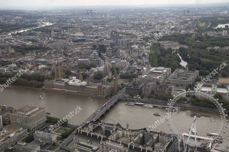 The London Eye/Millennium Wheel and The London Aquarium (below right) below The River Thames and Westminster Bridge and The Palace of Westminster (Elizabeth Tower/Big Ben, Victoria Tower, Houses of Parliament), and Portcullis House, (centre left). Westminster Abbey and Parliament Square (centre left), HM Treasury and St James's Park (right) and Buckingham Palace at the end of The Mall (top right)
