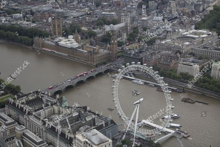 The London Eye/Millennium Wheel and The London Aquarium (below centre) below The River Thames and Westminster Bridge and The Palace of Westminster (Elizabeth Tower/Big Ben, Houses of Parliament), and Portcullis House, (centre right). Westminster Abbey and Parliament Square (centre), HM Treasury and St James's Park (top right)
