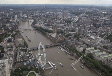 The London Eye/Millennium Wheel and The London Aquarium (below left) below The River Thames,  Westminster Bridge (nearest), Lambeth bridge, and Vauxhall Bridge (furthest). The Palace of Westminster (Elizabeth Tower/Big Ben, Houses of Parliament), and Portcullis House, (centre). Westminster Abbey and Parliament Square, HM Treasury (centre right)