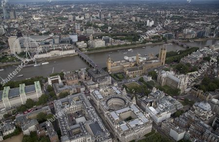 The river Thames, Westminster bridge and Parliament Square and Portcullis House next to The Palace of Westminster (Elizabeth Tower/Big Ben, Victoria Tower, Houses of Parliament), (top right) behind Westminster Abbey and Central Hall Westminster (centre right), HM Treasury (right), the Millennium wheel/London Eye and London Aquarium (top left).
