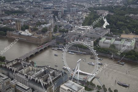 The River Thames passes under and Westminster Bridge. The London Eye/Millennium Wheel and The London Aquarium (below left) and The Palace of Westminster (Elizabeth Tower/Big Ben, Houses of Parliament), and Portcullis House, (centre). Westminster Abbey and Parliament Square (top left), HM Treasury and St James's Park and Buckingham Palace (top right)