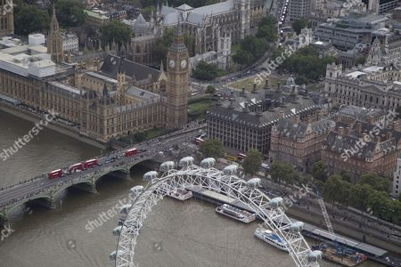 The River Thames passes under Westminster Bridge. The pods of the London Eye/Millennium Wheel below of The Palace of Westminster (Elizabeth Tower/Big Ben, Houses of Parliament), and Portcullis House, (centre). Westminster Abbey and Parliament Square (top centre).