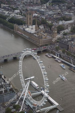 The River Thames passes under and Westminster Bridge. The London Eye/Millennium Wheel and The London Aquarium (below) and The Palace of Westminster (Elizabeth Tower/Big Ben, Victoria Tower, Houses of Parliament) (top centre), and and Portcullis House (right)  next to Westminster Abbey and Parliament Square.