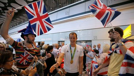 Gold medalist rower Matt Langridge, centre and other members of the Great Britain Olympic team are welcomed on return from the Olympics in Rio De Janeiro, at Heathrow Airport, in London