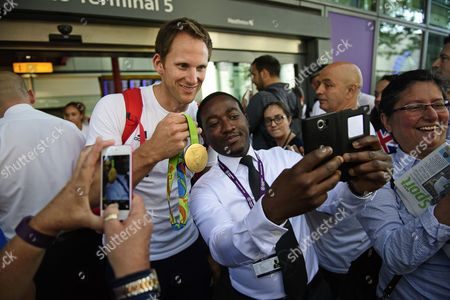 Matt Langridge,, Olympic gold medalist in the mens rowing eight, poses for members of the public with his gold medal as the team arrives at terminal 5 of London Heathrow Airport