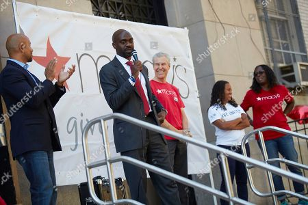 Macy's 11th Annual Give Back Day at the William Howard Taft Educational Complex in the Bronx borough of New York,. Assemblyman Michael Blake, center, addresses a crowd of 400 volunteers as Bronx Borough President Ruben Diaz Jr, left, and Macy's Chairman and CEO Terry J. Lundgren, right center, United Way CEO Sheena Wright, second from right, and Macy's SVP Bernice Clark, right, listen