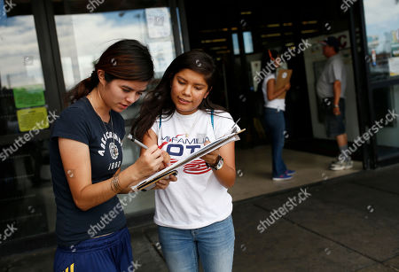 "Fabiola Vejar, right, registers Stephanie Cardenas to vote in front of a Latino supermarket in Las Vegas. Shielded from deportation under an Obama administration program that protects those brought to the country illegally as children, Vejar, 18, cannot vote. So she volunteers with Mi Familia Vota, encouraging others to be heard at the ballot box. ""I don't have that voice,"" she says, ""but there's other people ... who feel the way I do. They should vote"
