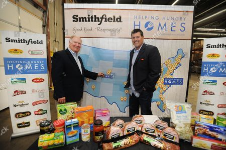Stock Image of Mark Schlereth, right, joins Dennis Pittman from Smithfield to mark the 23rd stop of Smithfield's 2016 nationwide Helping Hungry Homes tour at Food Bank of the Rockies on  in Denver