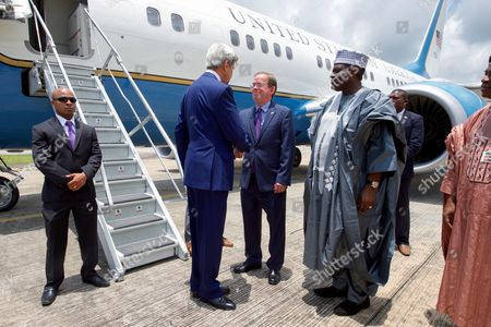 U.S. Secretary of State John Kerry shakes hands with U.S. Embassy Abuja Deputy Chief of Mission Lord Young