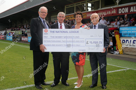 Stephanie Moore is presented with a cheque for the Bobby Moore Cancer charity by League officials Colin Peake, Brian Lee and Daggers MD Steve Thompson before Dagenham and Redbridge vs Wrexham, Vanarama National League Football at the Chigwell Construction Stadium on 27th August 2016