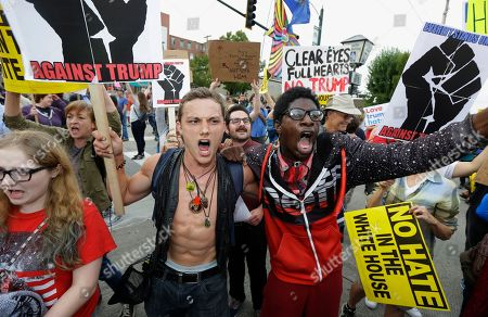 Gregory Vernon Enera III, center left, and Krystafer Oliver, center right, protest, outside a rally by Republican presidential candidate Donald Trump in Everett, Wash