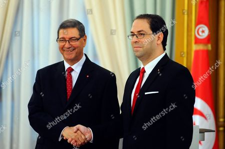 New Tunisian Prime Minister Youssef Chahed, right, shakes hands with former Prime Minister Habib Essid during the handover ceremony in Tunis, . Tunisia's Parliament has approved last week Chahed as prime minister along with a new government focused on boosting the economy and fighting terrorism