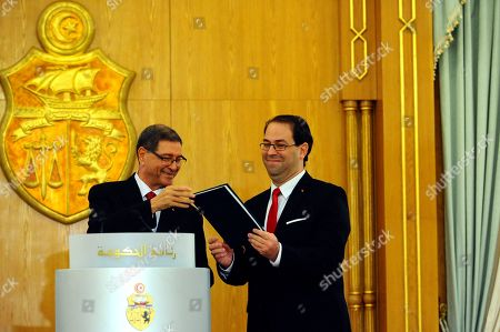 New Tunisian Prime Minister Youssef Chahed, right, holds a document given by former Prime Minister Habib Essid during the handover ceremony in Tunis, . Tunisia's Parliament has approved last week Chahed as prime minister along with a new government focused on boosting the economy and fighting terrorism