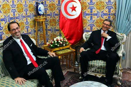 New Tunisian Prime Minister Youssef Chahed, left, smiles with with former Prime Minister Habib Essid during the handover ceremony in Tunis, . Tunisia's Parliament has approved last week Chahed as prime minister along with a new government focused on boosting the economy and fighting terrorism